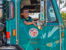 A happy youngster sits in a LA Sanitation refuse collection truck.